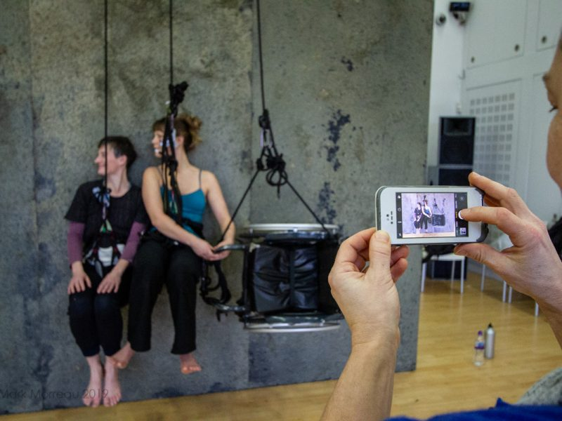 2 dancers suspended on a wall being filmed by someone with a camera phone